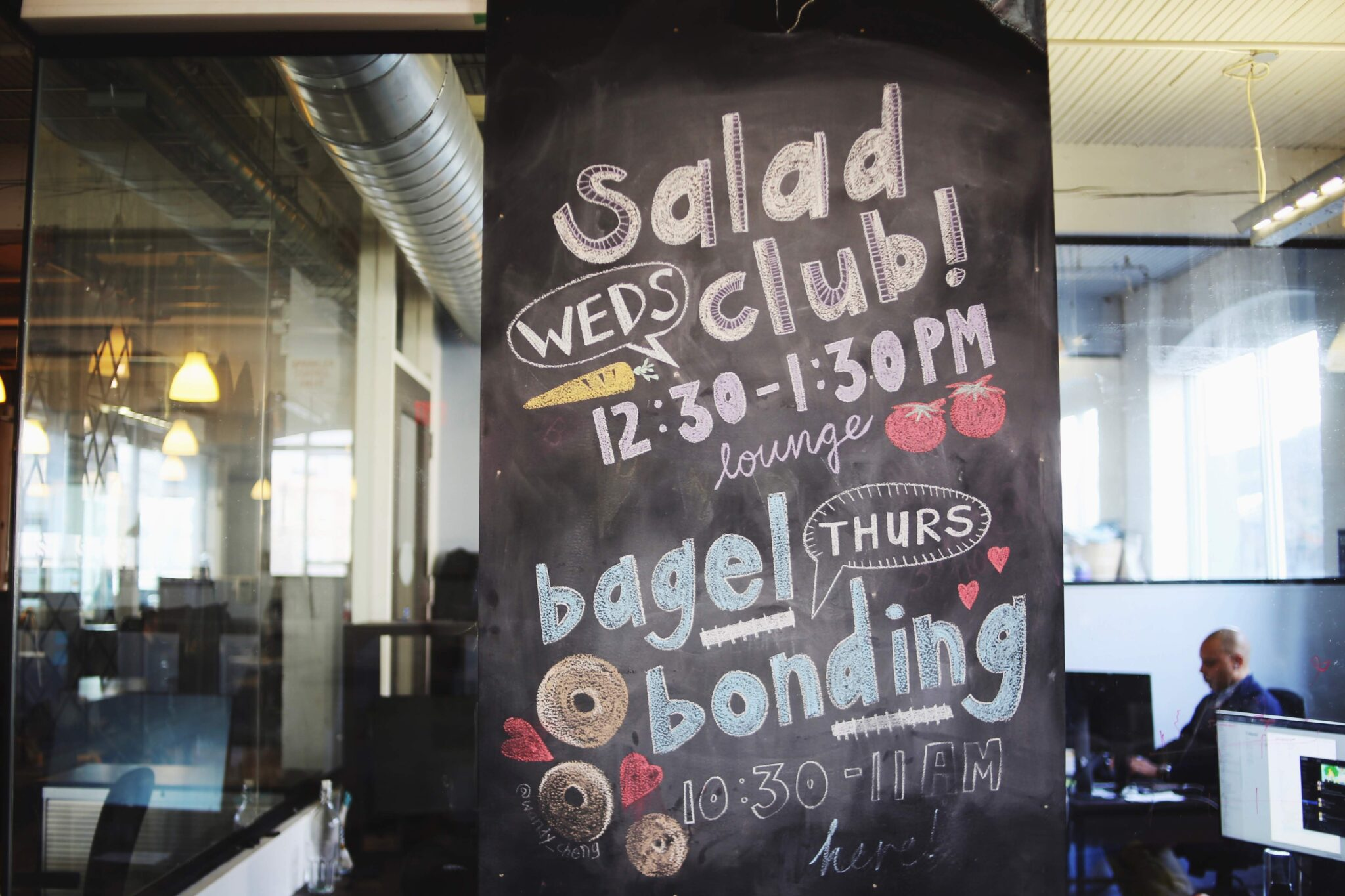 A chalkboard at the Centre for Social Innovation advertising Salad Club and Bagel Bonding