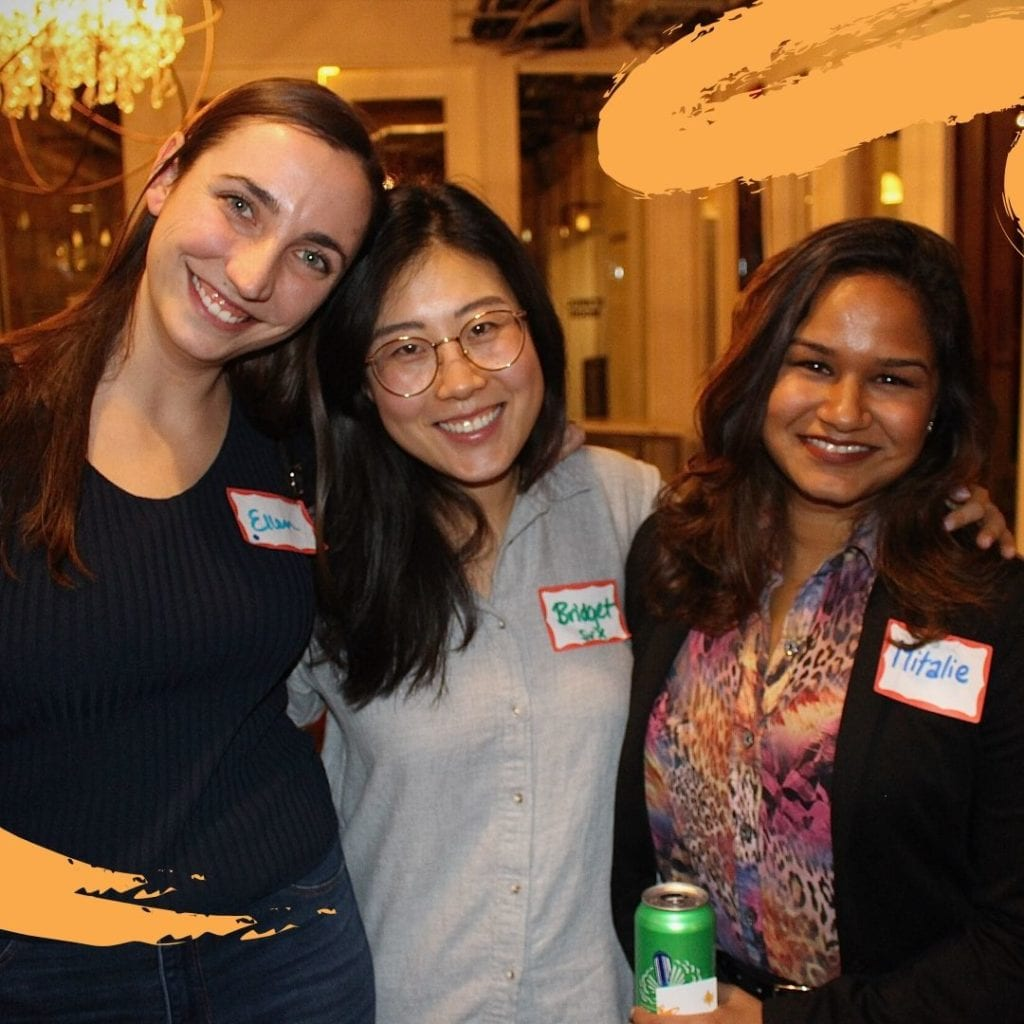 Three women from the WOSEN team smiling at the camera