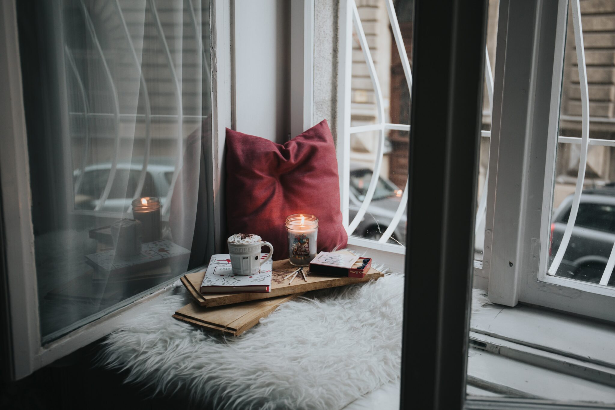 Photo of red couch pillow and cup of hot chocolate looking out through a window to the road
