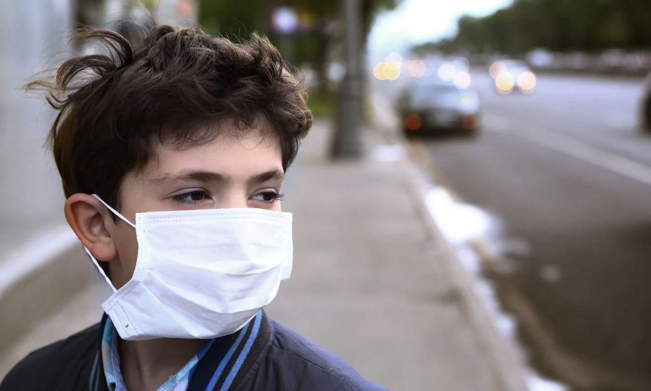 A boy with a surgical mask stares out into the street.