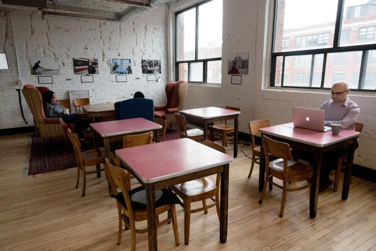 Members sitting at tables and couches in the fourth floor lounge at CSI Spadina. Photo credit: You the Best Photography.