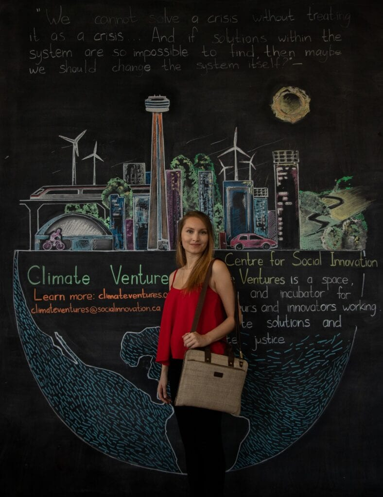 Person standing in front of a chalk board modelling a hemp bag