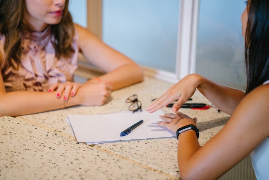 Two people sitting at a table and chatting. Focus is on hands with blank notepad.