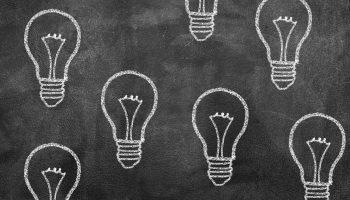 Lightbulbs drawn on dusty black chalkboard