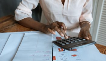 Person in a peach-coloured blouse sitting at a wooden desk using a black calculator. The desk is covered with notebooks and printouts with calculations.