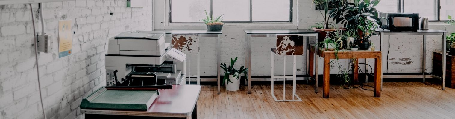 Printer, paper cutter, single desks in front of a window, plants, and microwave in the fourth floor lounge in CSI Spadina.