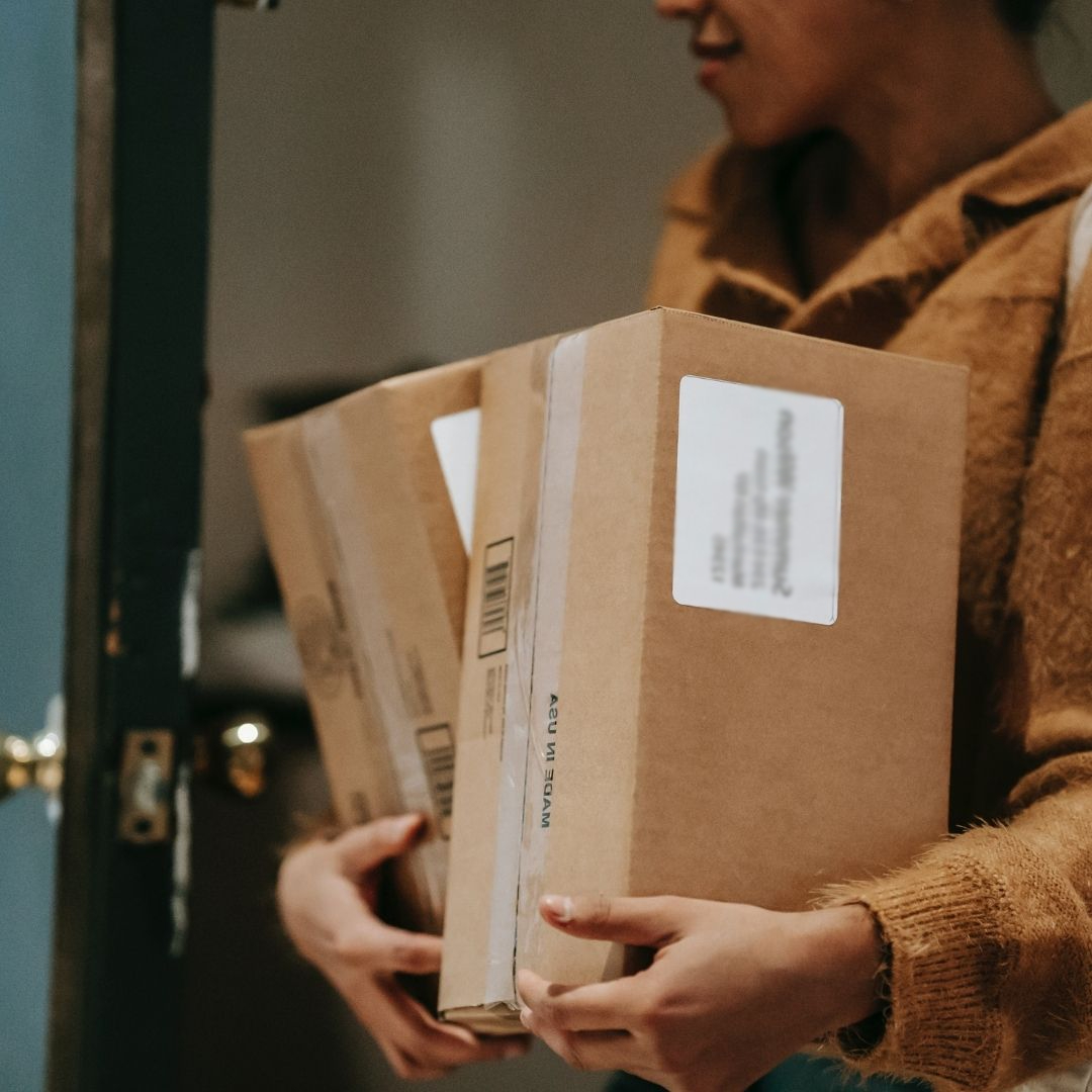 Person in brown coat carrying brown packages