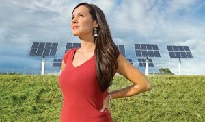 Melina Laboucan-Massimo standing in front of solar panels