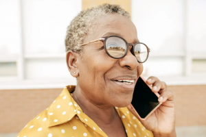 An older woman holding a phone up to her ear and smiling.