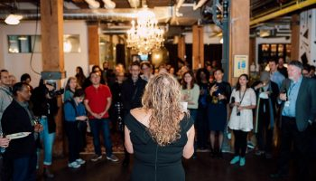 An audience gathered around CSI CEO Tonya Surman as she gives a speech in CSI Spadina.